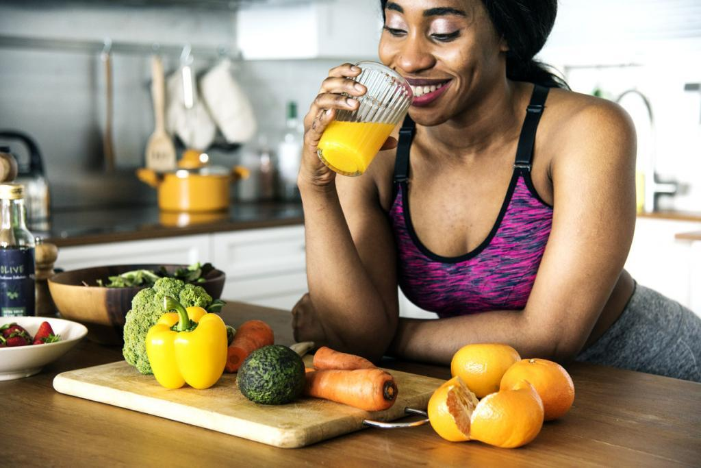 woman drinking orange juice with veggies in front of her